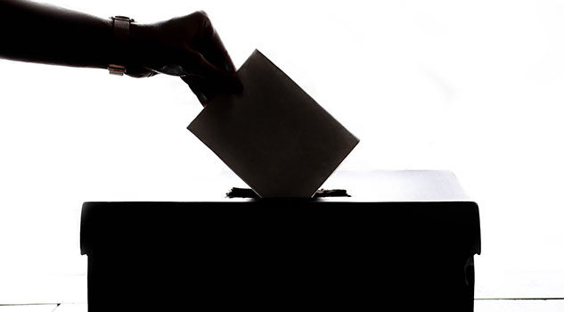 A silhouette of a hand putting a voter ballot into a box