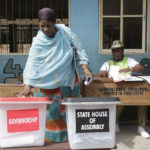 A woman casts her votes during the gubernatorial and state house assembly elections at a polling center in Makoko near Lagos
