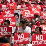 A group of protestors hold up 'no extradition signs'
