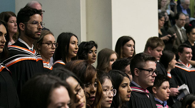 A group of graduates sit in Convocation Hall