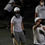 Men in white T-shirts with poles are seen in Yuen Long after attacked anti-extradition bill demonstrators at a train station, in Hong Kong, China