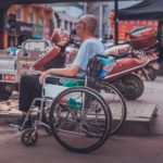 A man sits in a wheelchair at the market