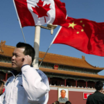 Man on phone standing in front of Canada and China flags