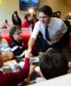 Justin Trudeau shaking the hand of a woman sitting in a diner booth