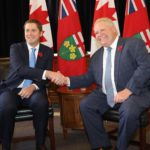 Andrew Scheer and Doug Ford sit side by side, shaking hands