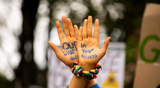 """A pair of hands with """"our lives are in your hands"""" written on the palms"""