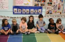 A group of pre-kindergarten students sit on the floor in their classroom