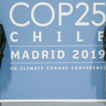 Rutu Patel, Naomi Butterfield, Emily Stutzman ad Grace Ma stand in front of COP25 poster