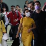 A group of people walk in public with surgical masks on