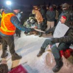 Police serve an injunction to protesters at a rail blockade in St-Lambert