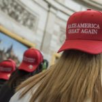 "A young woman wears a backwards ""Make America Great Again"" hat"
