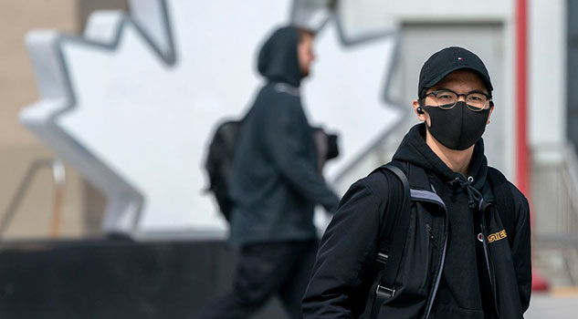 A man wears a face mask while walking in public