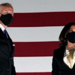 Joe Biden and Kamala Harris pose in front of the American flag, wearing masks.