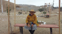 A woman from the Ihaunco settlement sits on a bench