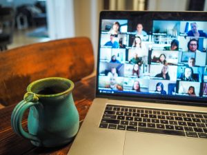 A coffee mug sits next to a computer with a Zoom meeting on the screen