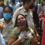 A crowd of people wearing masks stand in the street in India