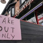 A take-out only sign affixed to the patio of a Toronto restaurant
