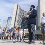 Jugmeet Singh gives a speech to a small crowd of people in front of Toronto's City Hall
